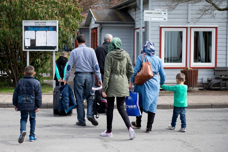 Refugees from Syria arrive at the Friedland shelter near Goettingen, central Germany, on April 4, 2016, after arriving from Turkey at the airport in Hanover. The first Syrians arrived in Germany from Istanbul under a controversial EU-Turkey migrant pact. / AFP PHOTO / dpa / Swen Pfoertner / Germany OUT