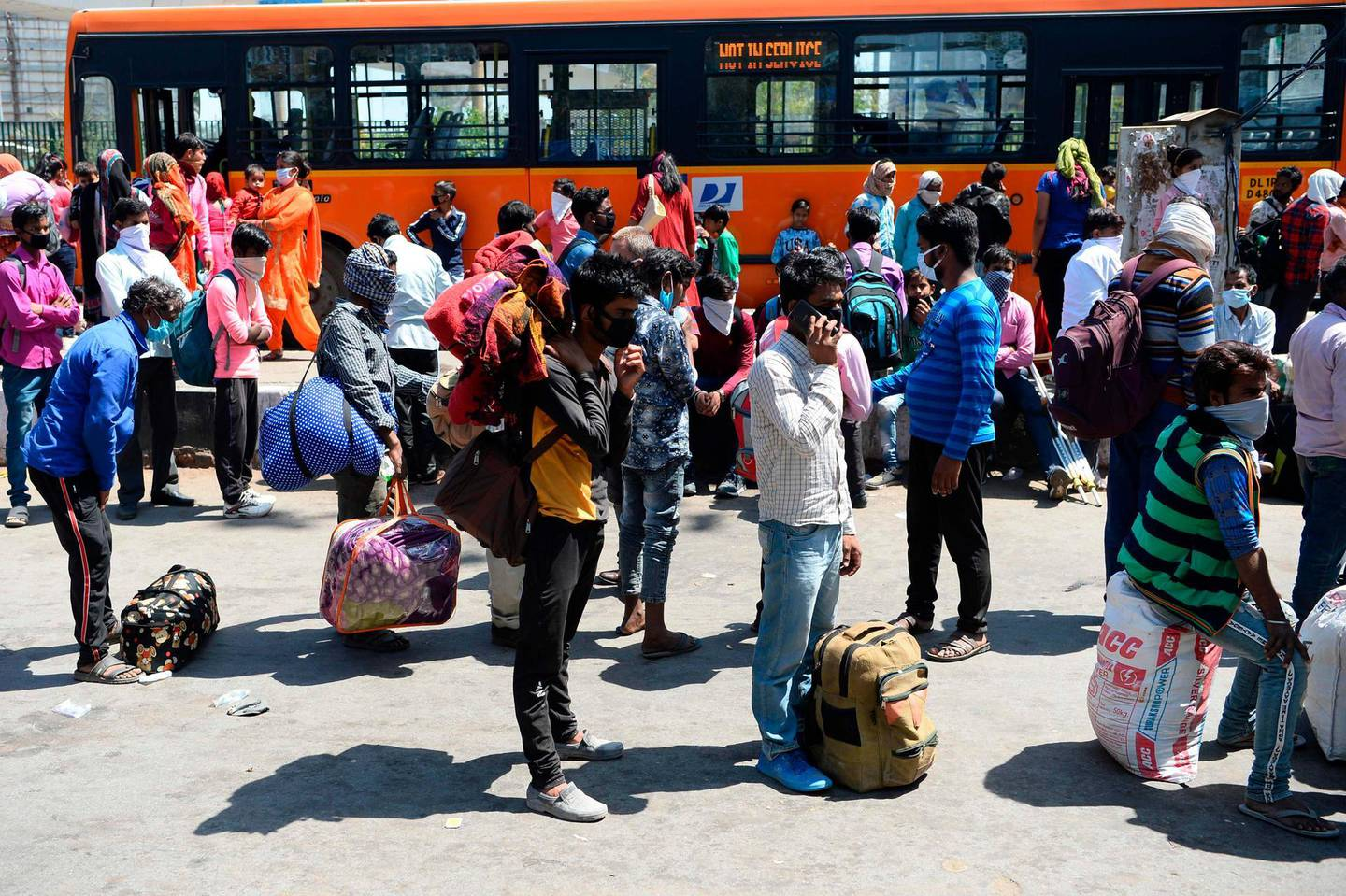 Migrant workers and their family members gather outside Anand Vihar bus terminal as they leave India's capital for their homes during a government-imposed nationwide lockdown as a preventive measure against the COVID-19 coronavirus, in New Delhi on March 29, 2020. / AFP / SAJJAD HUSSAIN