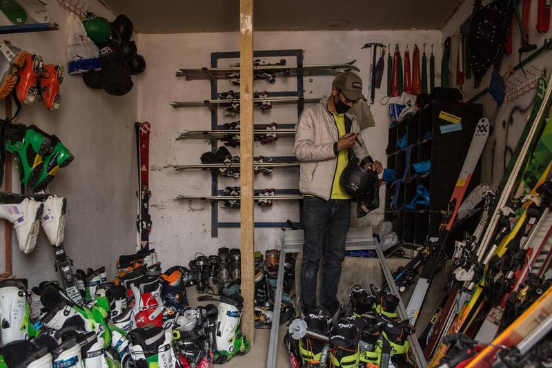 Said Ali Shah Farhang, 29, sorts through skiing equipment in his office, wearing a mask to protect from coronavirus risks.
