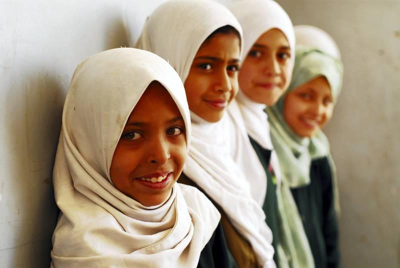 Yemen, Sanham, close-up portrait of smiling schoolgirls wearing headscarves standing together by wall