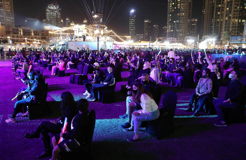DUBAI , UNITED ARAB EMIRATES , December 18 – 2020 :- People sitting on the chair and enjoying the performance of Anne Marie at the Burj Park in downtown Dubai on the second day of the DSF opening concert in Dubai.  ( Pawan Singh / The National ) For Arts & Culture/Online/Instagram. Story by Janice Rodrigues