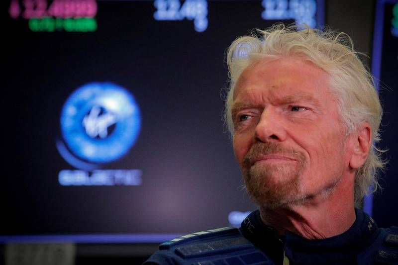 FILE PHOTO: Sir Richard Branson stands on the floor of the New York Stock Exchange ahead of the start of trading in Virgin Galactic in New York, Oct. 28, 2019. REUTERS/Brendan McDermid/File Photo
