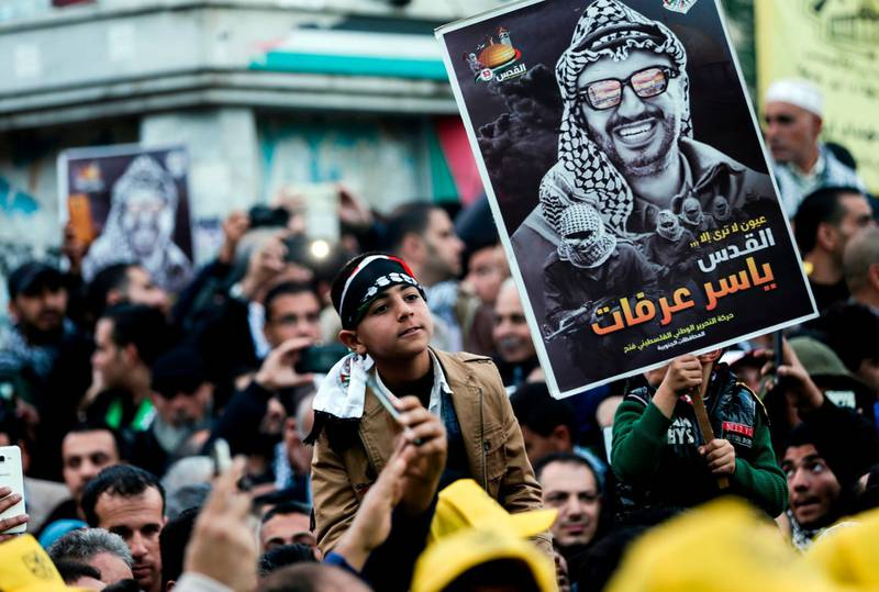 Supporters of the Fatah movement hold up a portrait of late Palestinian leader Yasser Arafat during a rally in Gaza City on December 31, 2017, marking the 53rd anniversary of the creation of the political party. / AFP PHOTO / MAHMUD HAMS