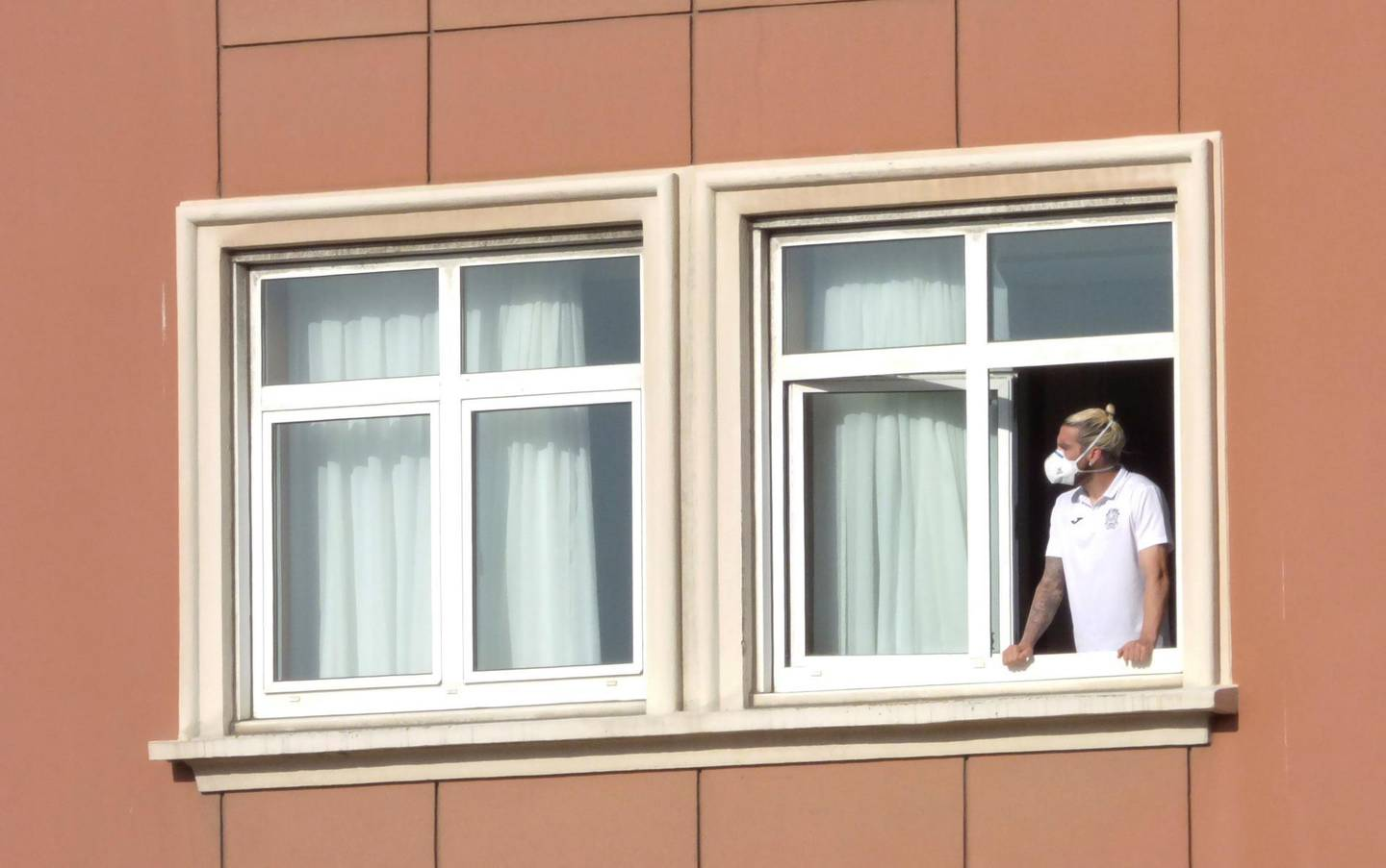 epa08559822 Spanish Second Division's CF Fuenlabrada team player Chico Flores looks from his room's window at the hotel where the team is confined in A Coruna, northwestern Spain, 22 July 2020. Six members of the team tested positive for COVID-19.  EPA/CABALAR