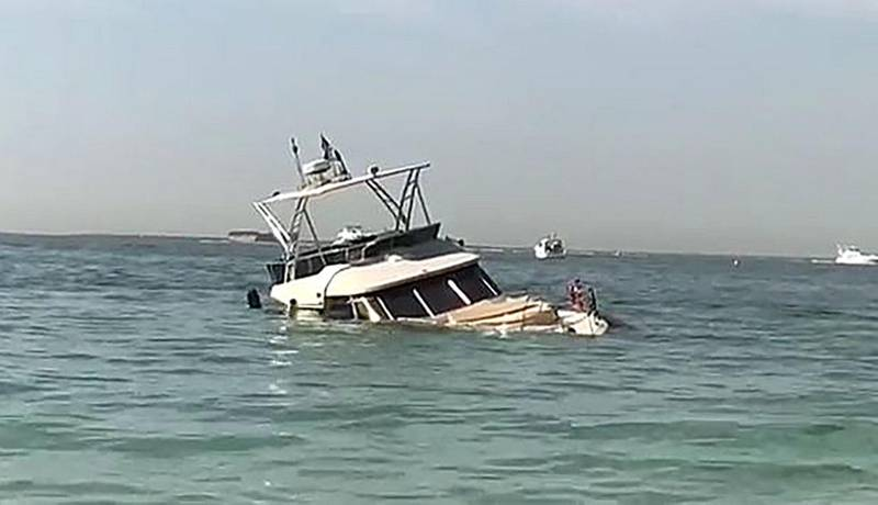 Yacht with the Russians turned over at the beach in Dubai