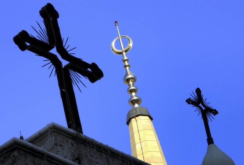 The Christian crosses of a Beirut cathedral surround a minaret of al Amin mosque in Beirut November 28, 2006. REUTERS/Eric Gaillard (LEBANON) - GM1DUAUJGFAA