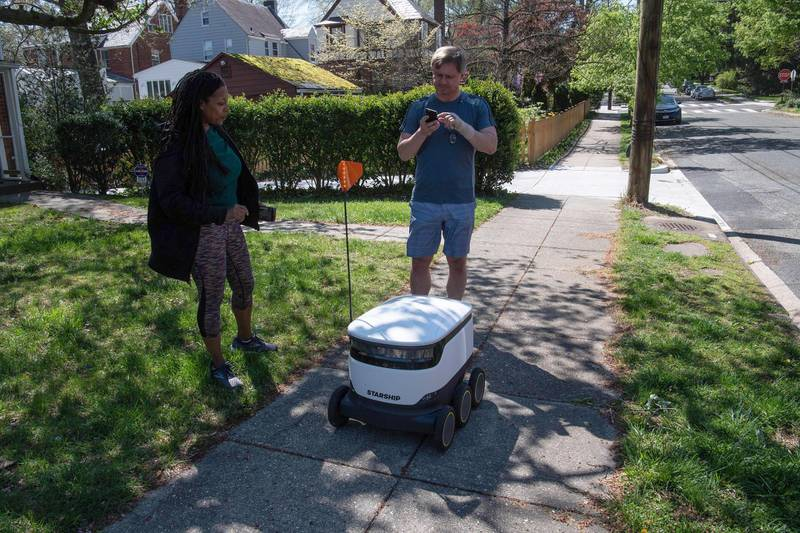 Kimmo Kartano uses his smartphone to open a food delivery robot from the Broad Branch Market grocery store as Audra Grant looks on in front of their house in the Chevy Chase neighborhood of Washington, DC, on April 9, 2020. - The store began using the robots about two weeks ago and makes 10-15 deliveries a day within a limited area of the neighborhood. (Photo by NICHOLAS KAMM / AFP)