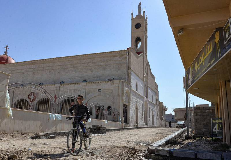 """A boy stands with his bicycle by the Syriac Catholic Church of the Immaculate Conception (al-Tahira-l-Kubra), in the predominantly Christian town of Qaraqosh (Baghdeda), in Nineveh province, some 30 kilometres from Mosul on February 24, 2021, ahead of Pope Francis' March visit to Iraq. Iraq's northern province of Nineveh is the heartland of the country's Christian community and its capital, Mosul, is where the Islamic State group chose to announce the establishment of its self-styled """"caliphate"""" in 2014. About 30 kilometres (20 miles) to the south lies Qaraqosh, also known as Baghdeda and Hamdaniya, which has a long pre-Christian history but whose residents today speak a modern dialect of Aramaic, the language of Jesus Christ. / AFP / Zaid AL-OBEIDI"""