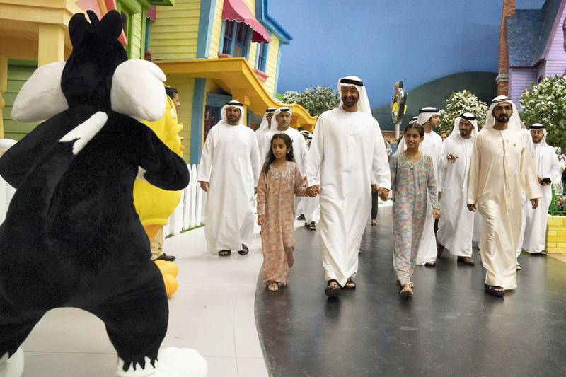 YAS ISLAND, ABU DHABI, UNITED ARAB EMIRATES - July 23, 2018: July 23, 2018:  HH Sheikha Fatima bint Mohamed bin Hamad bin Tahnoon Al Nahyan (L), HH Sheikh Mohamed bin Zayed Al Nahyan, Crown Prince of Abu Dhabi and Deputy Supreme Commander of the UAE Armed Forces (2nd L), HH Sheikha Salama bint Mohamed bin Hamad bin Tahnoon Al Nahya (3rd L) and HH Sheikh Mohamed bin Rashid Al Maktoum, Vice-President, Prime Minister of the UAE, Ruler of Dubai and Minister of Defence (R), attend the opening of Warner Bros World Abu Dhabi.   ( Hamad Al Kaabi / Crown Prince Court - Abu Dhabi ) ---