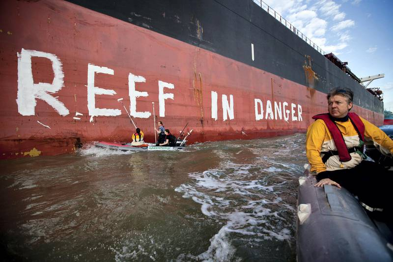 """GLADSTONE, AUSTRALIA - MARCH 7: In this handout photo provided by Greenpeace, Activists paint the message """"Reef in Danger"""" on the side of coal ship Chou San on March 7, 2012 in Gladstone, Australia. A delegation from UNESCO is arriving in Gladstone today to assess threats to the Great Barrier Reef, both existing projects and the expected increase in transport through the World Heritage area following a planned coal mine expansion. (Photo by Greenpeace via Getty Images)"""