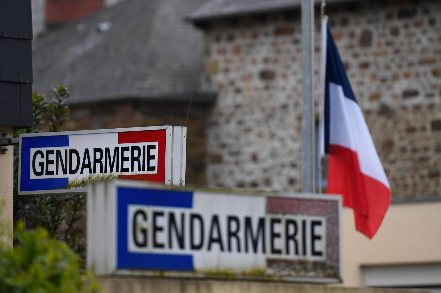 A French flag is seen lowered to half mast on March 24, 2018 at the gendarmerie in Hédé-Bazouges, suburb of Rennes, western France, as a tribute to French Lieutenant Colonel Arnaud Beltrame who was killed the day before after swapping himself for a hostage in a rampage and siege in the town of Trebes.  / AFP PHOTO / DAMIEN MEYER