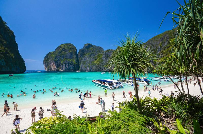 """In this March 4, 2017, photo, tourists enjoy the popular Maya bay on Phi Phi island, Krabi province. Authorities have ordered the temporary closing of the beach made famous by the Leonardo DiCaprio movie """"The Beach"""" to halt environmental damage caused by too many tourists. (AP Photo/Rajavi Omanee)"""