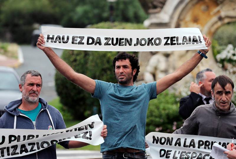 """Basque activists of """"No G7"""" hold banners reading 'This is not your playground' as they block the entry of Palace Hotel in Biarritz, southwestern France, Thursday Aug.15, 2019. The G7 will take place in Biarritz on Aug. 24-26, 2019. (AP Photo/Bob Edme)"""