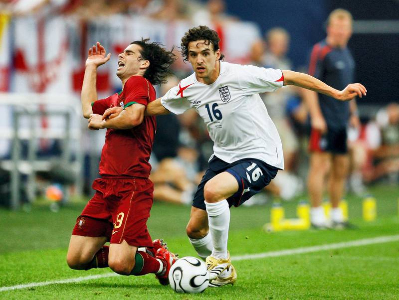 GELSENKIRCHEN, GERMANY - JULY 01: Tiago of Portugal falls to the ground as Owen Hargreaves of England surges forward during the FIFA World Cup Germany 2006 Quarter-final match between England and Portugal played at the Stadium Gelsenkirchen on July 1, 2006 in Gelsenkirchen, Germany. (Photo by Clive Mason/Getty Images)
