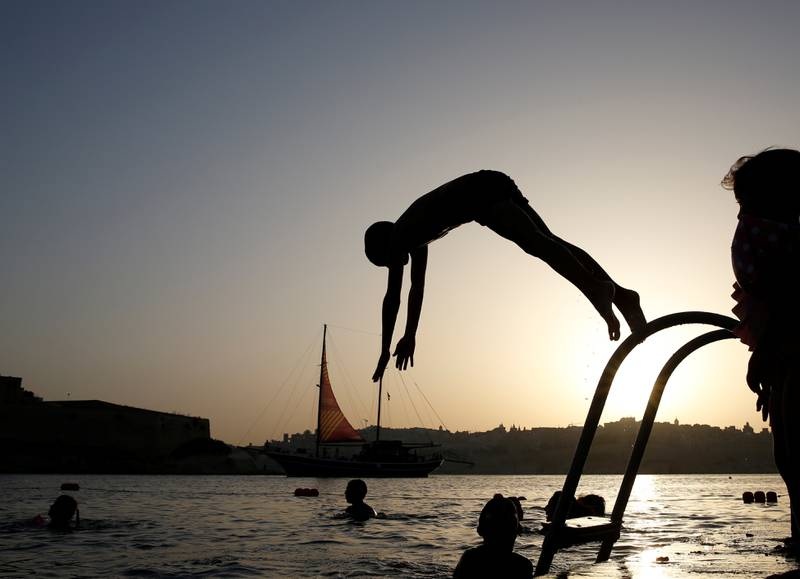 A boy dives into the sea as a Turkish gulet serving as a floating stage during the Malta International Arts Festival sails by, in Rinella Bay in the village of Kalkara, in Valletta's Grand Harbour, Malta, July 8, 2019.  REUTERS/Darrin Zammit Lupi