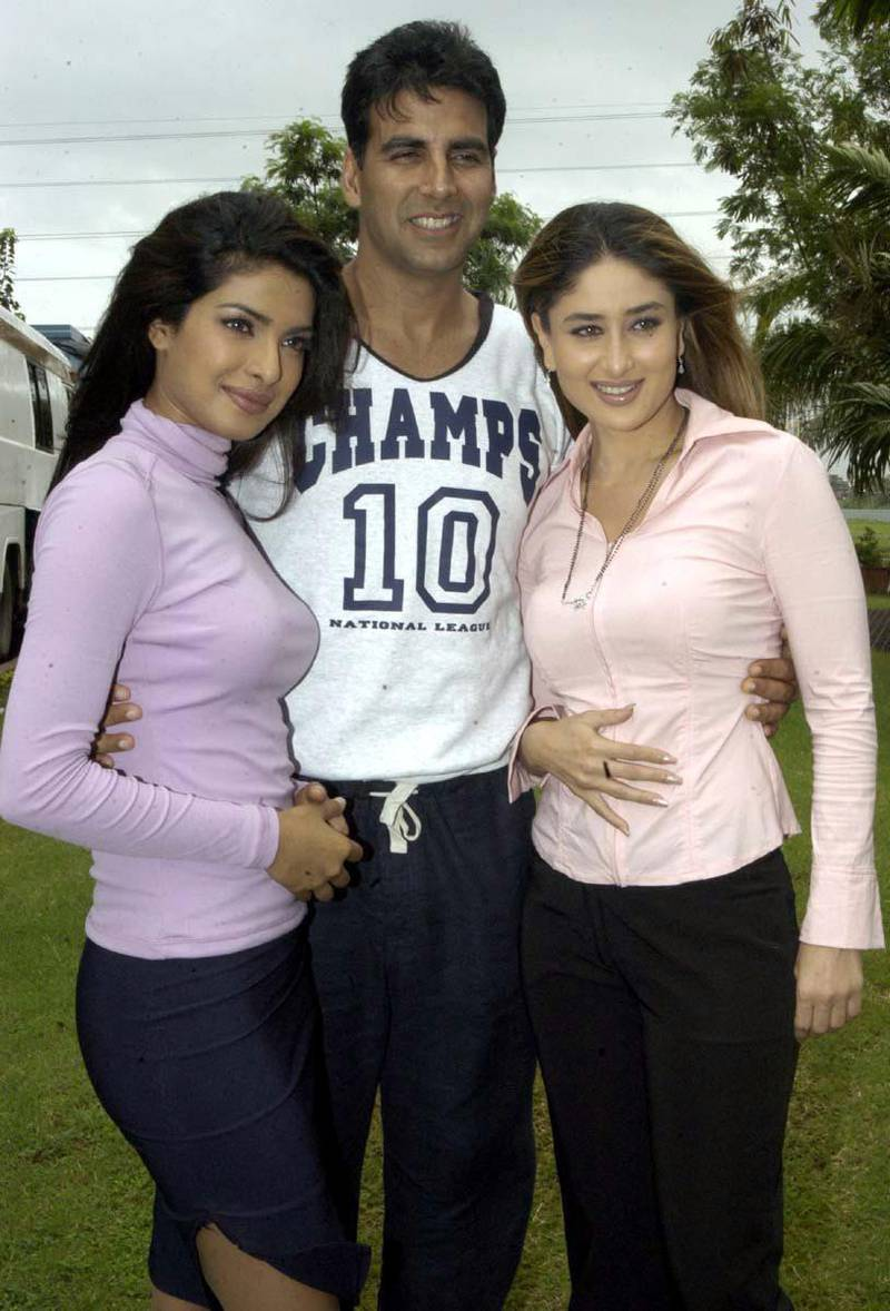 Bollywood actress Karina Kapoor (R) and Priyanka Chopra pose for photographers with Aksha  Kumar (C) during a film shoot in Bombay on Saturday, 10 July 2004. The actors are filming 'Aitraz' or objection, directed by Ammas Mastan.  EPA/STR