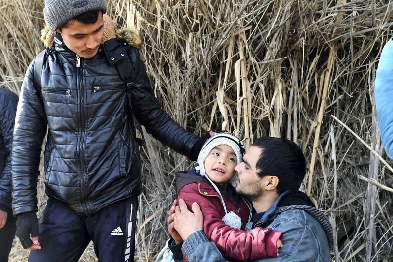 A man hugs a child upon their arrival at the village of Skala Sikaminias, on the Greek island of Lesbos, after crossing the Aegean sea from Turkey with other migrants, on Friday, Feb. 28, 2020. An air strike by Syrian government forces killed scores of Turkish soldiers in northeast Syria, a Turkish official said Friday, marking the largest death toll for Turkey in a single day since it first intervened in Syria in 2016. (AP Photo/Micheal Varaklas)