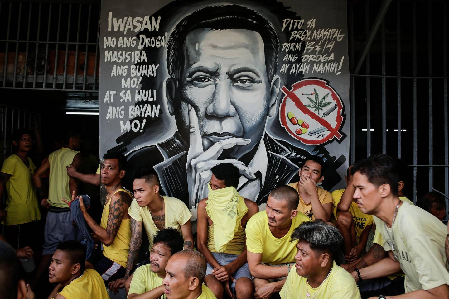 epa06268548 Inmates await clearance next to an image of Philippine President Rodrigo Duterte during a surprise inspection by the Bureau of Jail Management and Penology (BJMP) at the Manila City Jail in Manila, Philippines, 16 October 2017. The BJMP recovered several bladed weapons and illegal contrabands during the operation called 'Oplan Greyhound'.  EPA/MARK R. CRISTINO