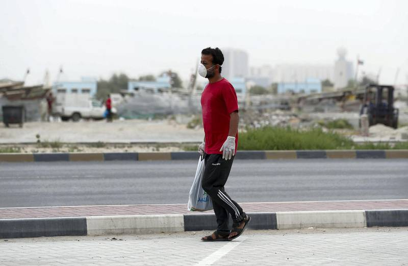 Ajman, United Arab Emirates - Reporter: N/A: A man walks passed fishing boats while wearing a facemask due to the Corona outbreak. Monday, April 13th, 2020. Ajman. Chris Whiteoak / The National