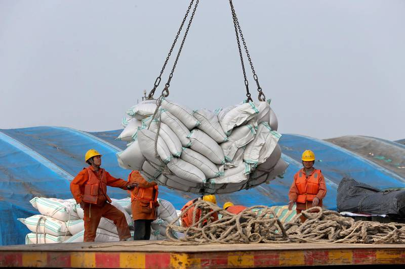 """In this March 22, 2018, photo, workers load imported soybeans at a port in Nantong in east China's Jiangsu province. China on Wednesday, April 4, 2018 vowed to take measures of the """"same strength"""" in response to a proposed U.S. tariff hike on $50 billion worth of Chinese goods in a spiraling dispute over technology policy that has fueled fears it might set back a global economic recovery. The Commerce Ministry said it would immediately challenge the U.S. move in the World Trade Organization. (Chinatopix via AP)"""
