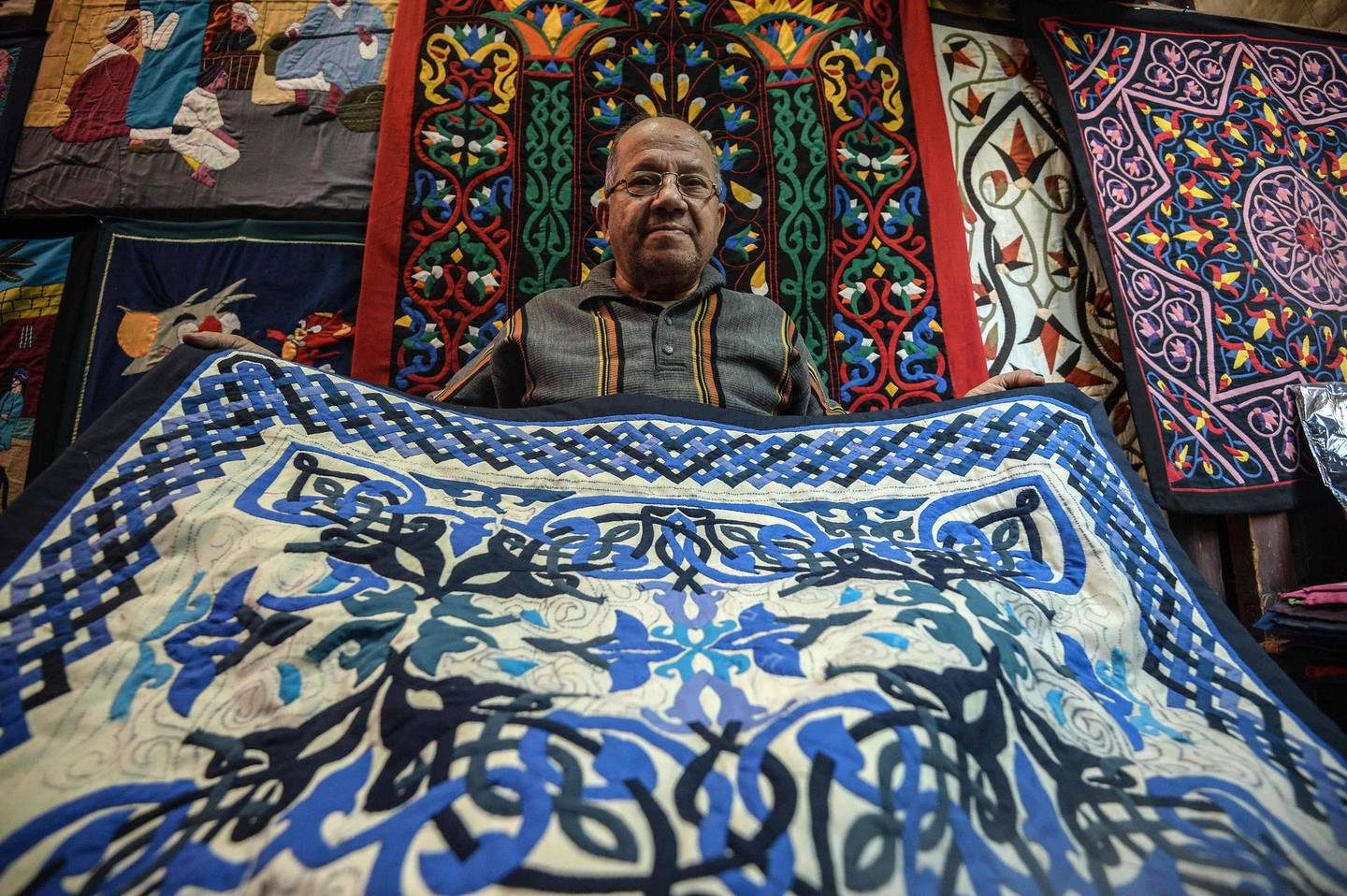 An Egyptian craftsman showcases a tapestry in his shop in Khayamiya Street, or the Street of Tent-makers, in the old city of the Egyptian capital Cairo on December 18, 2018. Along the sides of the roofed street of Khayamiya, or the Street of Tent-makers, dozens of craftsmen's shops have drawn foreign visitors for years until the 2011 uprising toppled longtime ruler Hosni Mubarak after which business has slowed to a trickle. The centuries-old art of Khayamiya, belived to have emerged during the Fatimid dynasty (10th-12th century AD), goes back to the time of travelling caravans, when huge tent pavilions were used as shields from the desert's searing sun. / AFP / Mohamed el-Shahed