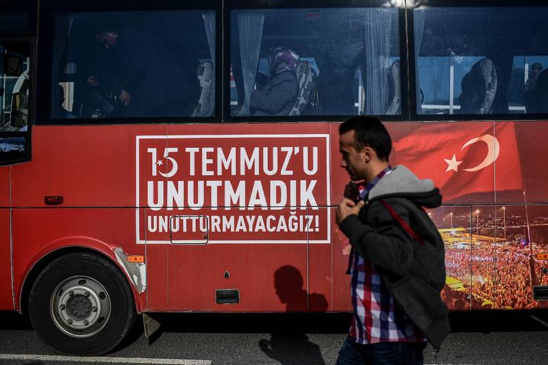 """A man passes by a bus with a message reading """"We do not forget July 15""""  by the Silivri prison courthouse, in Istanbul, on October 9, 2017, during a trial of 143 soldiers accused of causing the deaths of 34 people on Istanbul's first Bosphorus bridge on the night of last year's failed coup. Almost 150 former Turkish military personnel go on trial Monday over clashes on an Istanbul bridge during last year's failed coup that claimed dozens of lives including a key aide of President Recep Tayyip Erdogan. The bridge across the Bosphorus strait in Istanbul was the scene of bloody fighting between Erdogan's supporters and renegade soldiers seeking to oust the elected government on the night of July 15, 2016. / AFP PHOTO / OZAN KOSE"""