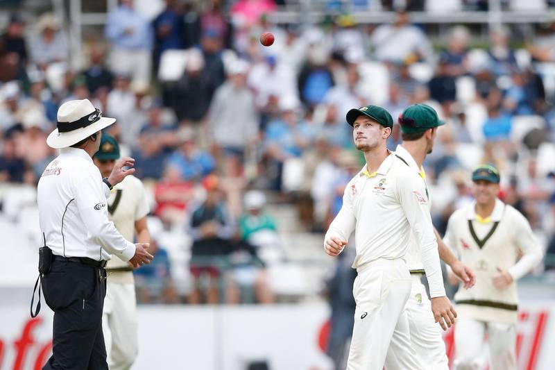 Australian fielder Cameron Bancroft (R) throws the ball to Umpire Richard Illingworth (L) during the third day of the third Test cricket match between South Africa and Australia at Newlands cricket ground on March 24, 2018 in Cape Town. / AFP PHOTO / GIANLUIGI GUERCIA