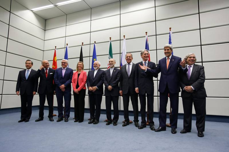 """(From L to R) Chinese Foreign Minister Wang Yi, French Foreign Minister Laurent Fabius, German Foreign Minister Frank-Walter Steinmeier, European Union High Representative for Foreign Affairs and Security Policy Federica Mogherini, Iranian Foreign Minister Mohammad Javad Zarif, Head of the Iranian Atomic Energy Organization Ali Akbar Salehi, Russian Foreign Minister Sergey Lavrov, British Foreign Secretary Philip Hammond, US Secretary of State John Kerry and US Secretary of Energy Ernest Moniz pose for a group picture at the United Nations building in Vienna, Austria July 14, 2015. Iran and six major world powers reached a nuclear deal, capping more than a decade of on-off negotiations with an agreement that could potentially transform the Middle East, and which Israel called an """"historic surrender"""".      AFP PHOTO / POOL / CARLOS BARRIA (Photo by CARLOS BARRIA / POOL / AFP)"""