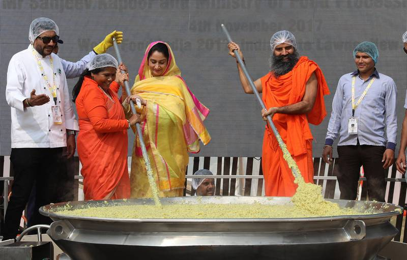 epa06307645 Indian renowned Chef Sanjeev Kapoor (L), Indian Union Minister for Food Processing and Member of Parliament (MP), Harsimrat Kaur Badal (C), Minister for Food Processing Sadhvi Niranjan Jyoti (2-L ) and Indian Yoga Guru Baba Ramdev (2-R) stir khichdi, an Indian traditional staple dish in a wok during an attempt to make a world record at World Food India 2017 in New Delhi, India, 04 November 2017. According to news report, Indian Chefs attempted a World record by cooking around 800 kilograms of  khichdi, an Indian traditional staple dish  at World Food India 2017. Later the dish was distributed to the underprivileged people in Delhi.  EPA/RAJAT GUPTA