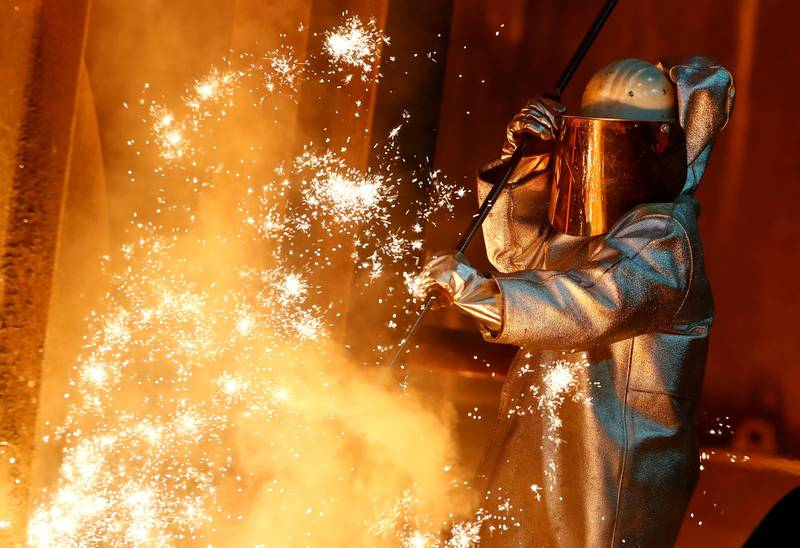 FILE PHOTO: A steel worker of ThyssenKrupp stands amid sparks of raw iron coming from a blast furnace at a ThyssenKrupp steel factory in Duisburg, western Germany, January 30, 2020. REUTERS/Wolfgang Rattay/File Photo