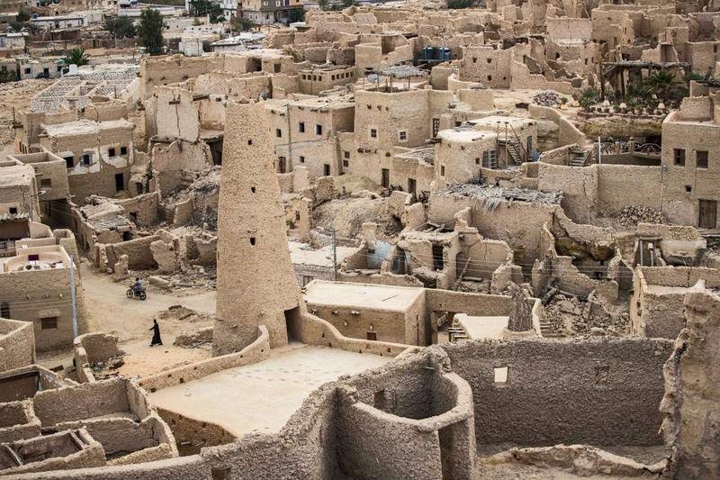 """This picture shows a view of the recently restored fortress of Shali and its surroundings, in the Egyptian desert oasis of Siwa, some 600 kms southwest of the capital Cairo, on November 6, 2020. - The 13th century edifice, called Shali or """"Home"""" in the Siwi language, was built by Berber populations, using kershef, a mixture of clay, salt and rock which acts as a natural insulator in an area where the summer heat can be scorching.After it was worn away by erosion, and then torrential rains in 1926, the European Union and Egyptian company Environmental Quality International (EQI) from 2018 sought to restore the building, at a cost of over $600,000. (Photo by Khaled DESOUKI / AFP)"""