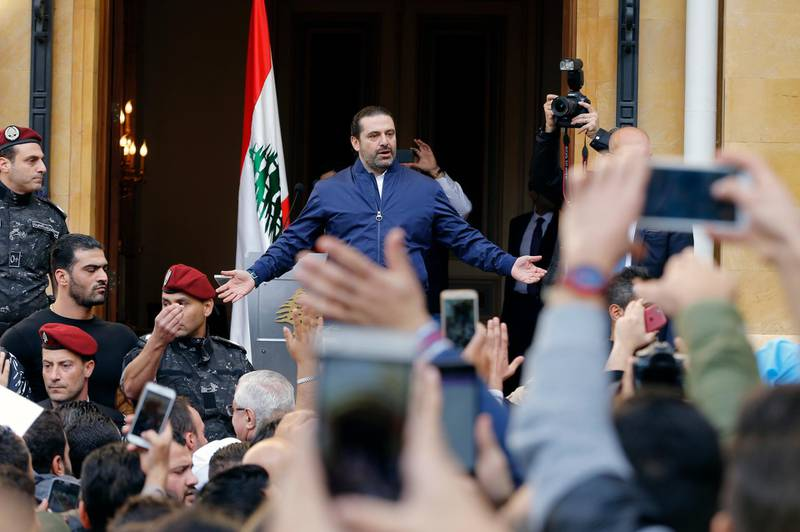 Lebanese Prime Minister Saad Hariri sings the Lebanese national anthem with thousands of his supporters who rallying outside his residence in Beirut, Lebanon, Wednesday, Nov. 22, 2017. Hariri said he was putting his resignation on hold responding to a request from the president to give more time to consultations. (AP Photo/Bilal Hussein)