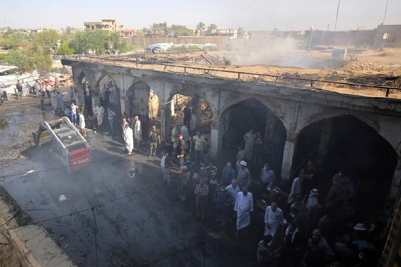 Iraqis look at the damage at aftermath scene of a mortar and bombing attack on the Sayyid Mohammed shrine in the Balad area, located 70 kilometres (around 45 miles) north of Baghdad, on July 8, 2016. - The Islamic State group carried out the attack on the Shiite shrine that killed 30 people, the jihadist-linked Amaq agency said. It came just five days after a suicide bomber detonated an explosives-rigged minibus in the capital, killing 292 people. (Photo by AHMAD AL-RUBAYE / AFP)