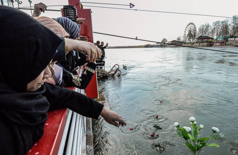 Iraqi women cast flowers into the Tigris river in remembrance for the victims of the capsized ferry in the northern Iraqi city of Mosul on March 22, 2019, following the incident which left at least 100 people dead, as the ferry was packed with families celebrating Kurdish New Year.    / AFP / Zaid AL-OBEIDI