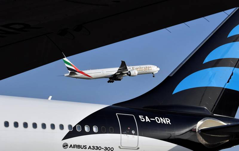 An Emirates Airline Boeing 777 aircraft is seen next to an Airbus A330-300 as it takes off from the Felix Houphouet-Boigny Airport in Abidjan on November 28, 2017. / AFP PHOTO / ISSOUF SANOGO