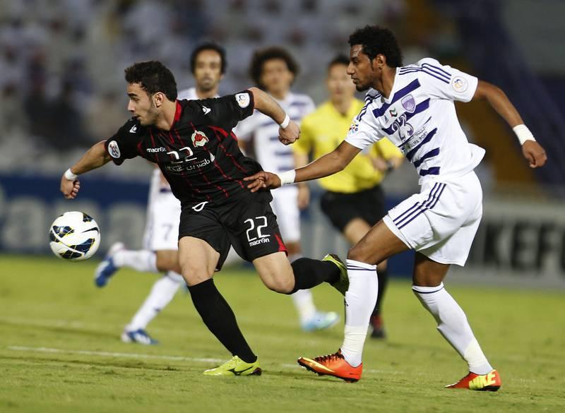 Mohamed Ahmed Gharib (R) of UAE's Al-Ain club vies for the ball with Ahmed Alaaeldin (L) of Qatar's Al-Rayyan club during their AFC Champions League football match in the eastern Emirati city of Al-Ain on April 3, 2013. AFP PHOTO /KARIM SAHIB  *** Local Caption ***  832428-01-08.jpg