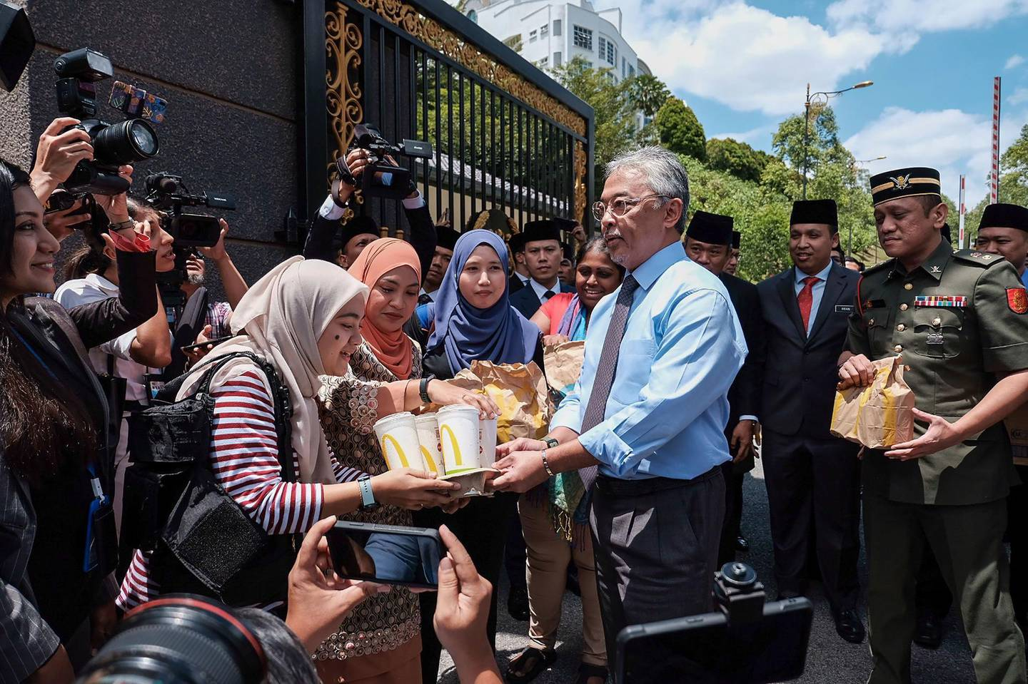 Malaysia's King Sultan Abdullah Sultan Ahmad Shah (centre R) hands out packages of fast food to reporters standing outside the National Palace in Kuala Lumpur on February 25, 2020. Intense political jockeying is underway to form a new government in Malaysia after Mahathir Mohamad, the world's oldest leader, resigned then was appointed interim leader. / AFP / Syaiful Redzuan