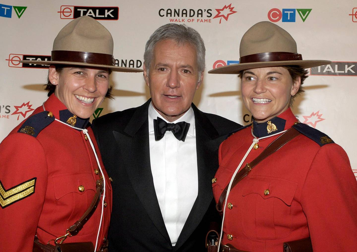 epa08808373 (FILE) - TV game show host Alex Trebek (C) poses with Canadian Mounties Mia Poscente (L) and April Dequanne backstage at the ninth annual Canada's Walk of Fame ceremony in Toronto, Canada, 03 June 2006 (reissued 08 November 2020). Alex Trebek, legendary host of TV game show Jeopardy, has died on 08 November 2020 at the age of 80, media report.  EPA/WARREN TODA
