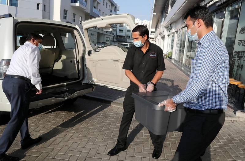 DUBAI , UNITED ARAB EMIRATES , November 25 – Staff members of the Vasai Local restaurant loading food box in the car outside the restaurant in Al Karama area in Dubai. Vasai Local Restaurant is providing food for the campaign run by St Mary Church which are giving meals to the poor or those who lost their jobs. ( Pawan Singh / The National ) For News/Online. Story by Patrick