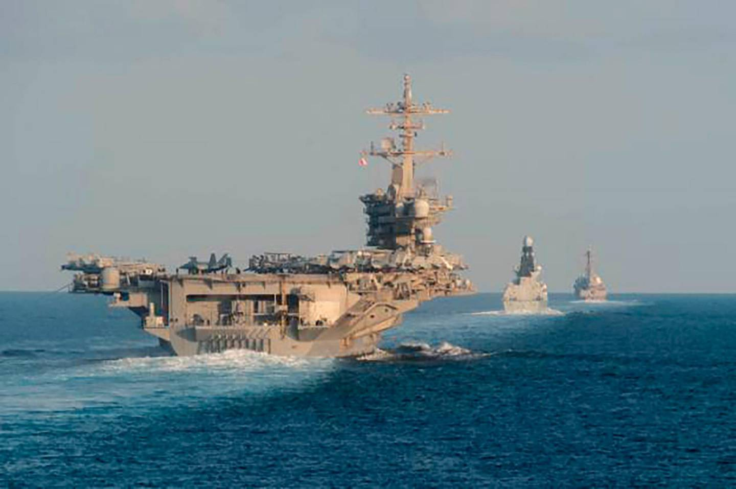 In this Tuesday, Nov. 19, 2019, photo made available by U.S. Navy, the aircraft carrier USS Abraham Lincoln, left, the air-defense destroyer HMS Defender and the guided-missile destroyer USS Farragut transit the Strait of Hormuz with the guided-missile cruiser USS Leyte Gulf. The U.S. aircraft carrier Abraham Lincoln sent to the Mideast in May over tensions with Iran transited the narrow Strait of Hormuz for the first time on Tuesday. The ship previously had been in the Arabian Sea outside of the Persian Gulf. (Mass Communication Specialist 3rd Class Zachary Pearson/U.S. Navy via AP)