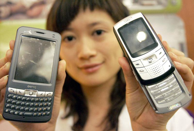 A Chinese promotion girl shows off the latest mobile phones from Taiwan's BenQ, at a launch in Beijing, 08 June 2005.  Taiwan's BenQ Corp said it aims to secure 10 percent of China's cellphone handset market in three years after the company won a permit to sell its products on its own on the mainland, as previously, BenQ relied on its joint venture with China-based CEC Telecom Co for sales of its handsets under a dual-brand strategy on the mainland.         AFP PHOTO (Photo by STR / AFP)