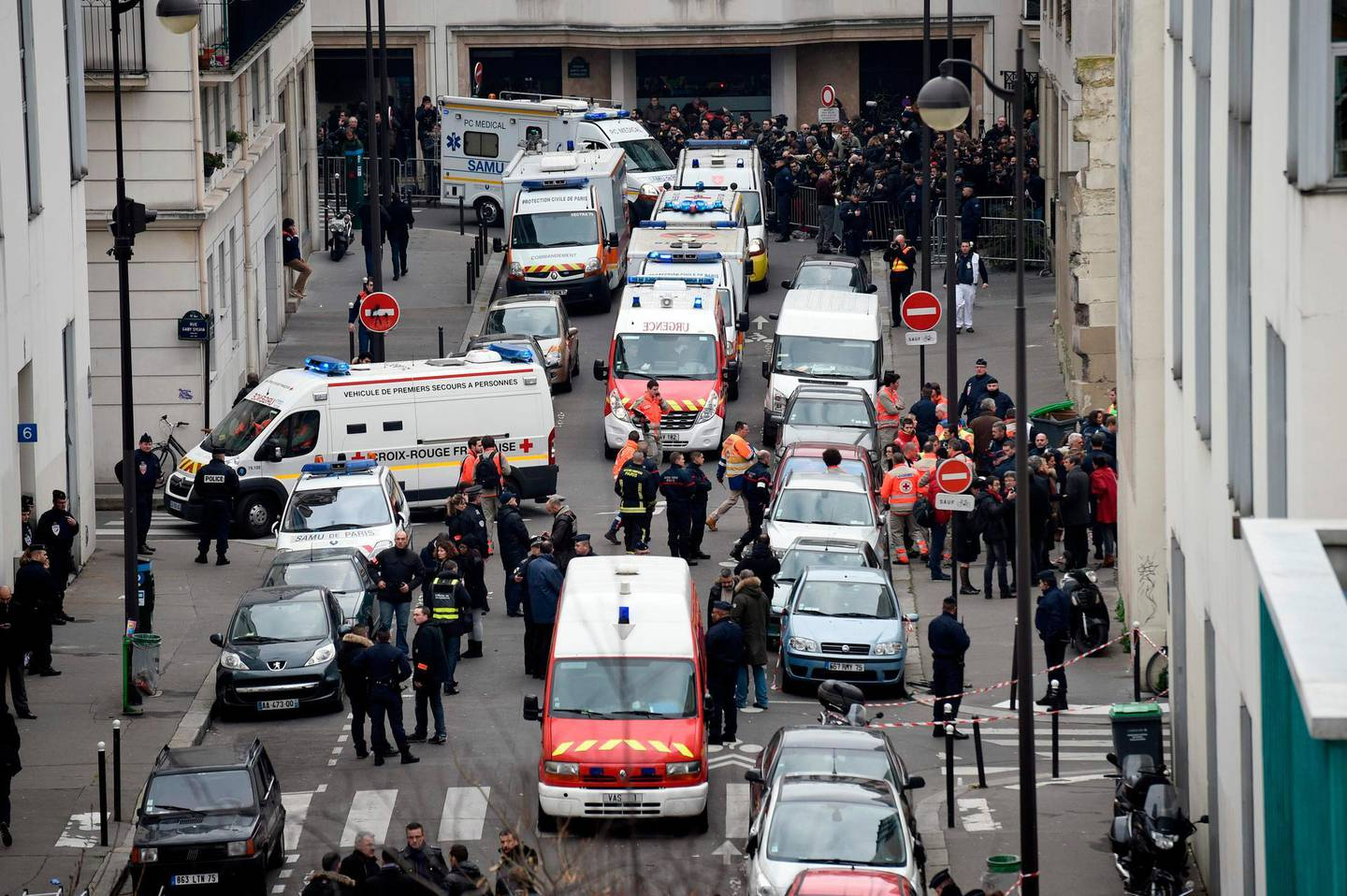 (FILES) This file photo taken on January 7, 2015 shows a general view of firefighters, police officers and forensics gathered in front of the offices of the French satirical newspaper Charlie Hebdo in Paris, after the brothers Kouachi stormed the offices leaving twelve dead.  The trial of the January 2015 attacks on Charlie Hebdo, Montrouge and Hyper Cacher will take place from September 2 to November 10, 2020 in Paris. / AFP / Martin BUREAU
