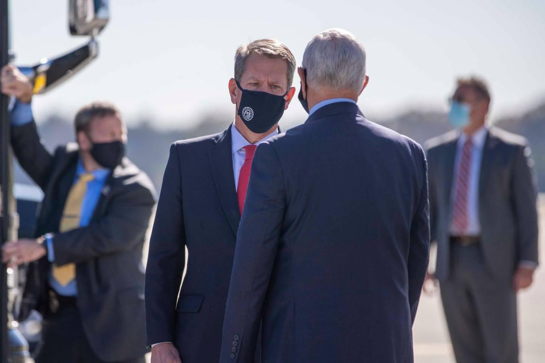 Vice President Mike Pence is greeted by Georgia Gov. Brian Kemp as he arrives at Dobbins Air Reserve Base in Marietta, Ga., Friday, Nov. 20, 2020. (Alyssa Pointer /Atlanta Journal-Constitution via AP)