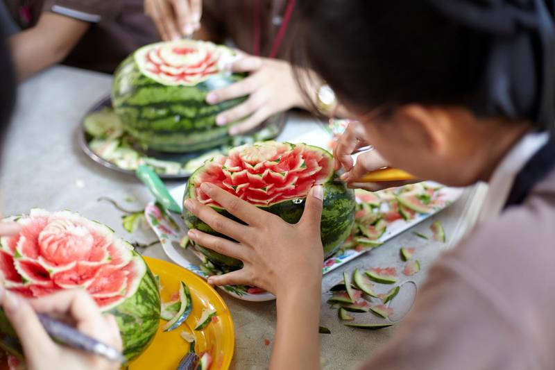 Bangkok-Thailand-CLC (Community Learning Center) Temple of Dawn- Close up of student hands craving on the water melon. Sasamon Rattanalangkarn for The National