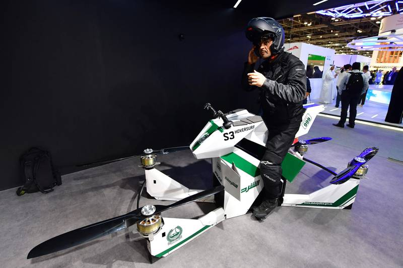 An Emiratee police officer stands next to a drone motorcycle at the Gitex 2017 exhibition at the Dubai World Trade Center in Dubai on October 8, 2017.  / AFP PHOTO / GIUSEPPE CACACE