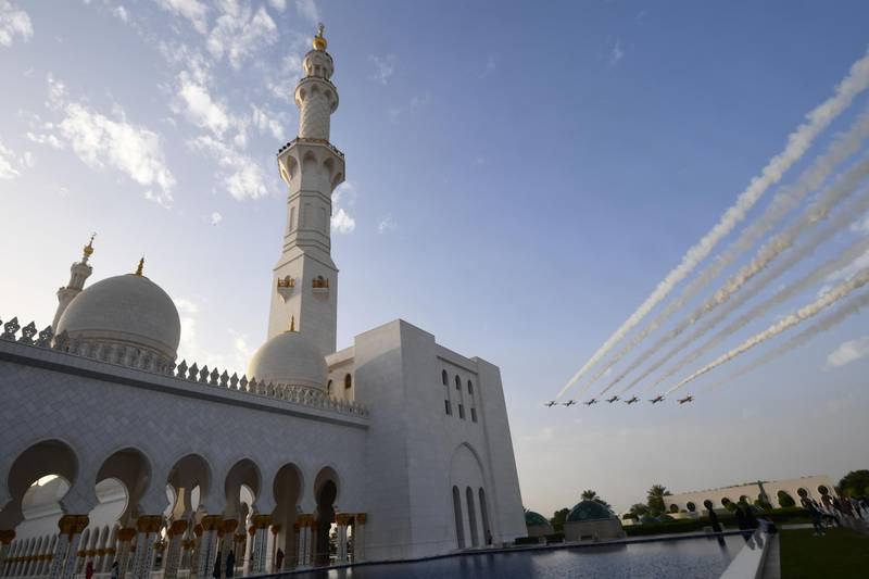 A picture taken on November 6, 2018 shows Aermacchi MB-339 jets from UAE's Al-Fursan flying over the the Sheikh Zayed Grand Mosque in the Emirati capital Abu Dhabi. / AFP / GIUSEPPE CACACE