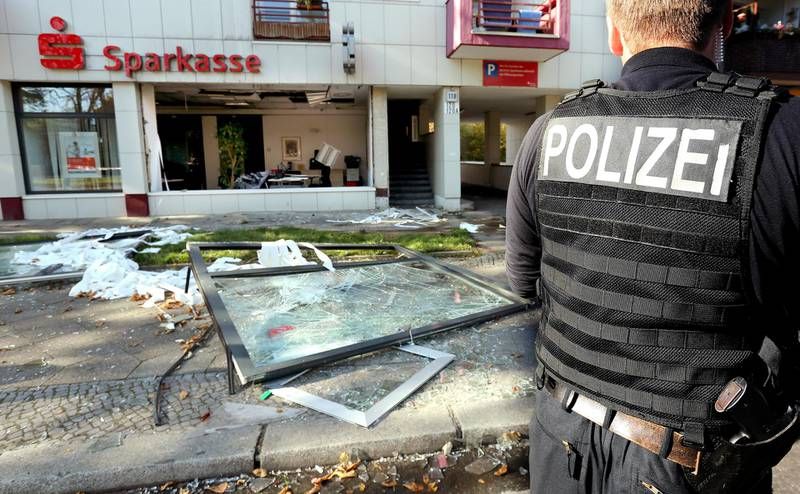 Policemen search for traces in front of a Sparkasse branch in Berlin, Germany, 10 October 2014. Unknowns triggered an exploison in the branch and cleared several lockers. Photo: Wolfgang Kumm/dpa | usage worldwide   (Photo by Wolfgang Kumm/picture alliance via Getty Images)