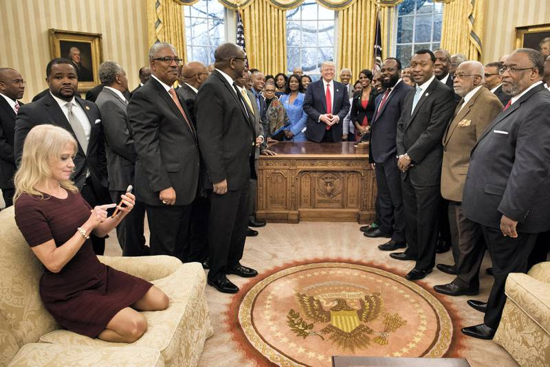Counselor to the President Kellyanne Conway (L) checks her phone after taking a photo as US President Donald Trump and leaders of historically black universities and colleges pose for a group photo in the Oval Office of the White House before a meeting with US Vice President Mike Pence February 27, 2017 in Washington, DC. (Photo by Brendan Smialowski / AFP)