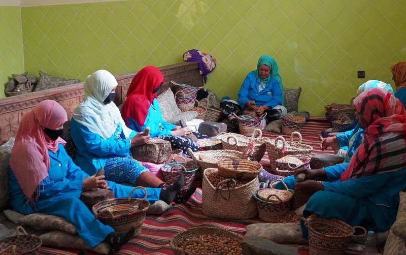 Amazigh women sit together as they crush argan nuts to extract the kernels, at Women's Agricultural Cooperative Taitmatine, in Tiout, near Taroudant, Morocco June 10, 2021. Picture taken June 10, 2021. REUTERS/Abdelhak Balhaki