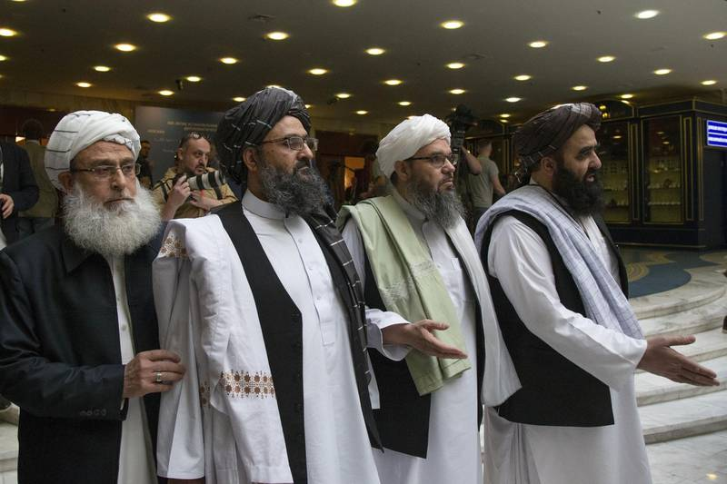FILE - In this May 28, 2019 file photo, Mullah Abdul Ghani Baradar, the Taliban group's top political leader, second left, arrives with other members of the Taliban delegation for talks in Moscow, Russia. Afghanistan's Taliban leaders agreed they wanted a deal with the United States, but some among them were in more of a hurry than others. Even before U.S. President Donald Trump cancelled a mysterious Camp David summit on Saturday, Sept. 7, 2019, the Taliban negotiators were at odds with the council of leaders, or shura, that rules the Islamic movement. (AP Photo/Alexander Zemlianichenko, File)